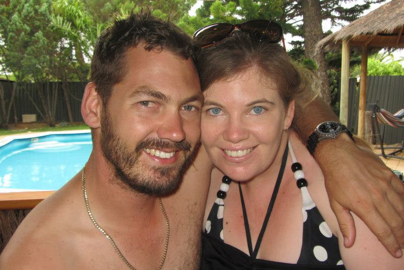 A man with a beard has his arm around a lady with sunglasses, pool in background.