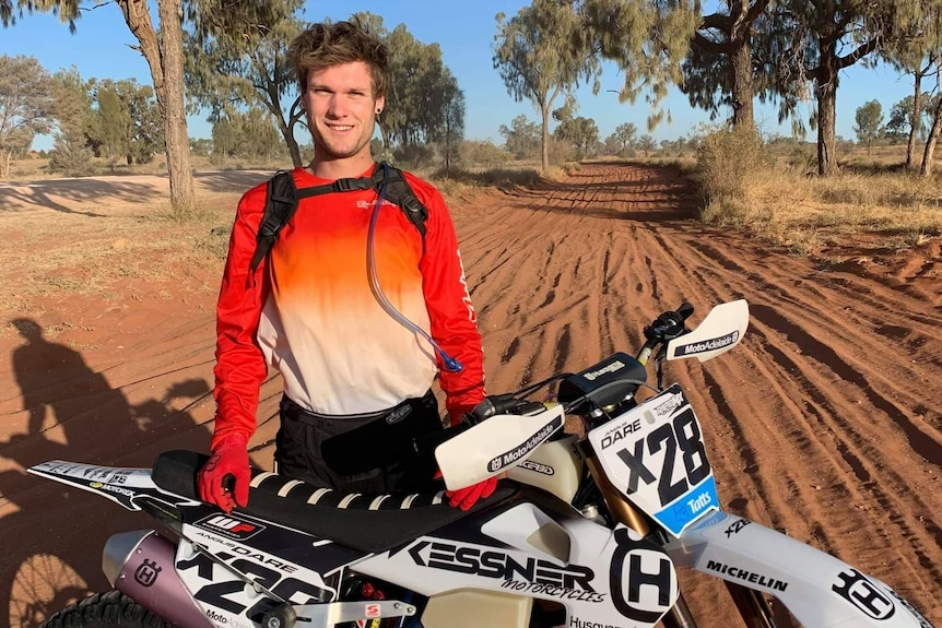 A man wearing an orange shirt stands with his white dirt bike on a red dirt road with gum trees in the background