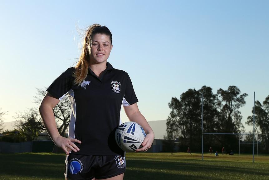 Kaarla Cowan stands on a football field holding a football.