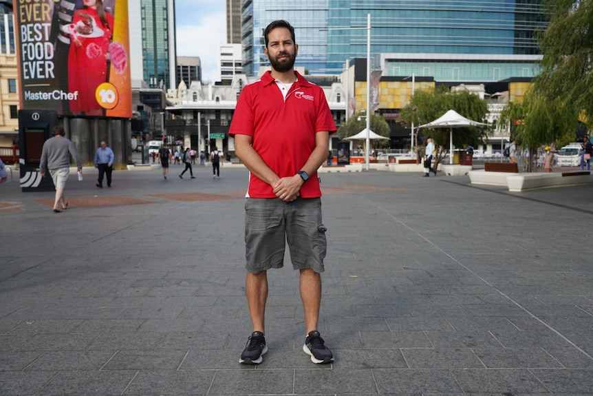 A walking tour operator stands in the middle of the Perth CBD with his arms crossed and a serious expression