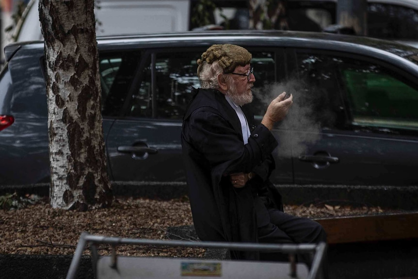 A barrister in a wig and black silks sitting down and smoking.