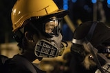 A person wearing a yellow helmet, clear goggles and a gas mask at night.