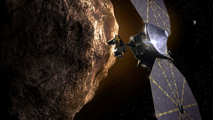 An artist's impression of the Lucy spacecraft flying by a Trojan asteroid.