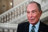 Michael Bloomberg stands outside a building