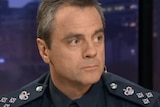 Stuart Bateson, wearing a police uniform, looks to his left while sitting on the set of Q&A