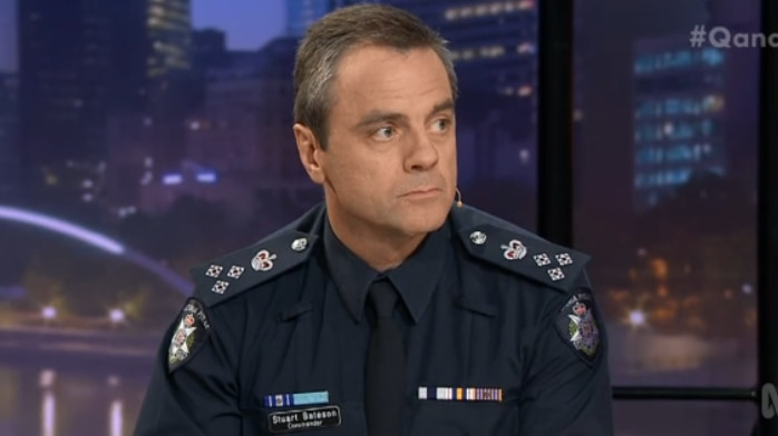 Stuart Bateson, wearing a police uniform looks to his left while sitting on the set of Q&A