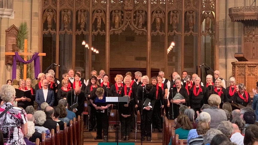 A choir stands in front of an audience in a cathedral