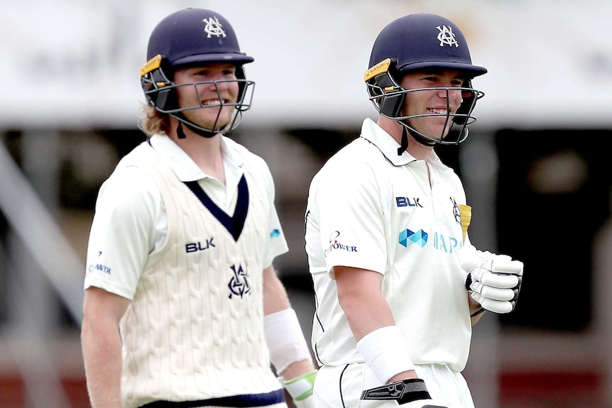 Two Victorian batters walk off the field smiling during a Sheffield Shield match against South Australia.