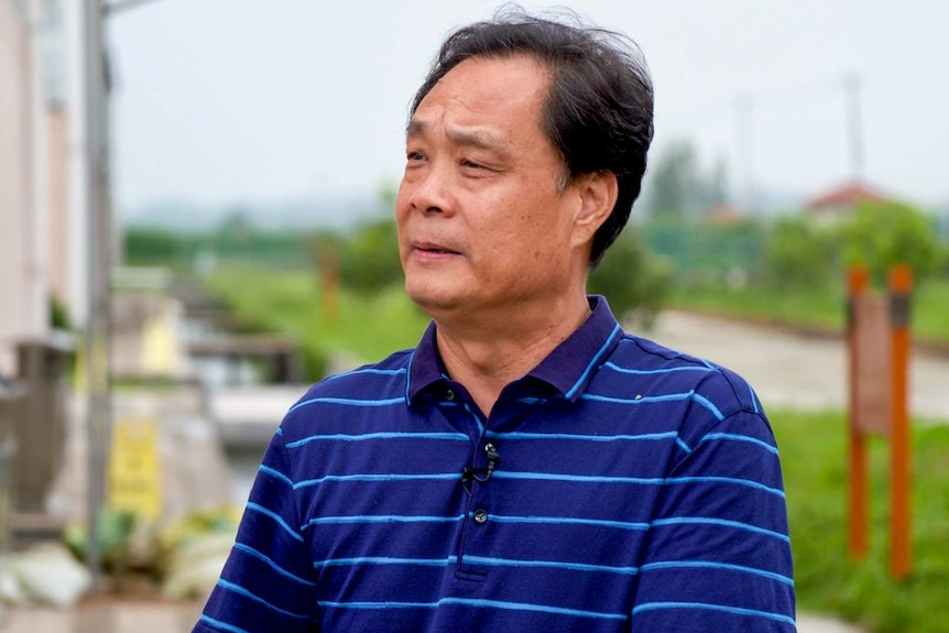A man in a polo shirt stands outside a factory building
