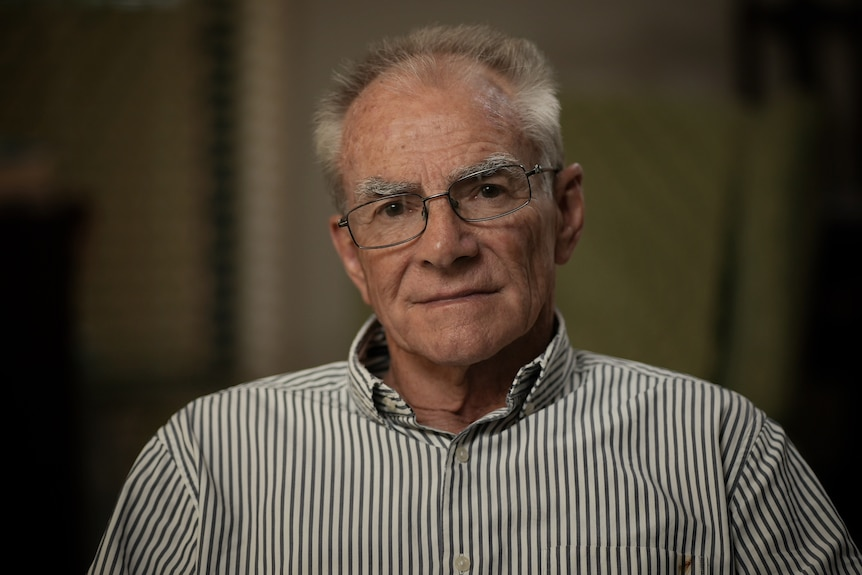 An older man in a stripey shirt and glasses looks unimpressed.