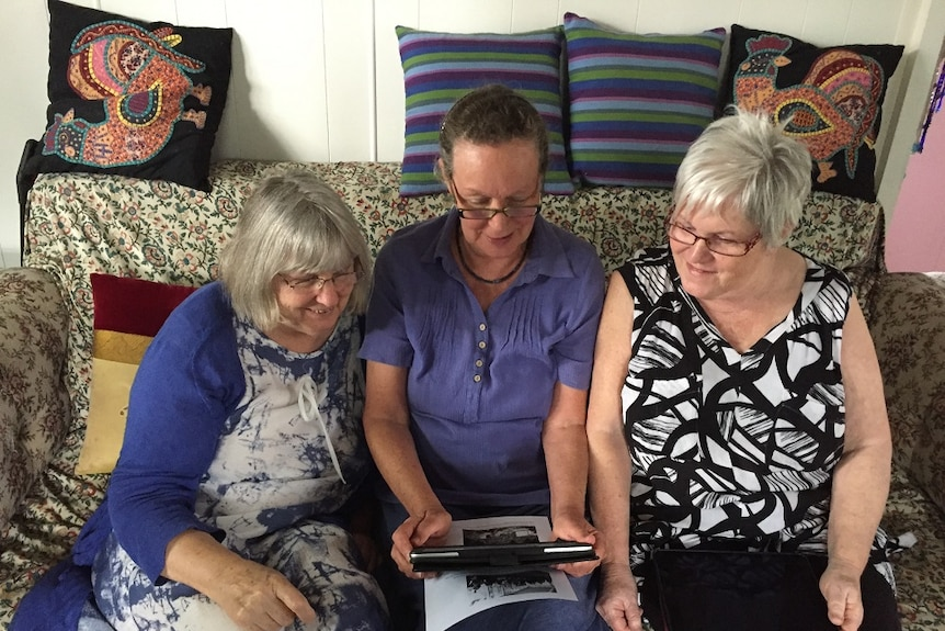 Melita Luck, Bridget Carr and Janet Wilson sitting on a couch talking to refugees on Manus Island via Facebook.