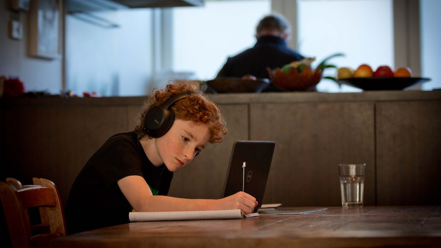 A child is writing on a notepad and wearing headphones while studying from home.