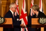 Malcolm Turnbull and Theresa May smile and shake hands during a news conference at Downing Street.