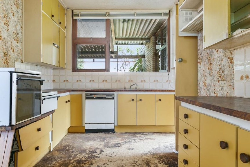 A dated kitchen with damaged yellow cupboards and floral wallpaper.