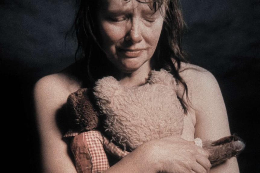 Photo of nude woman holding teddy bear