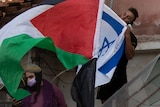 A man kisses the Israeli flag as protesters wave the Palestinian flag