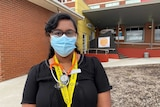 A young female doctor standing outside a hospital emergency department