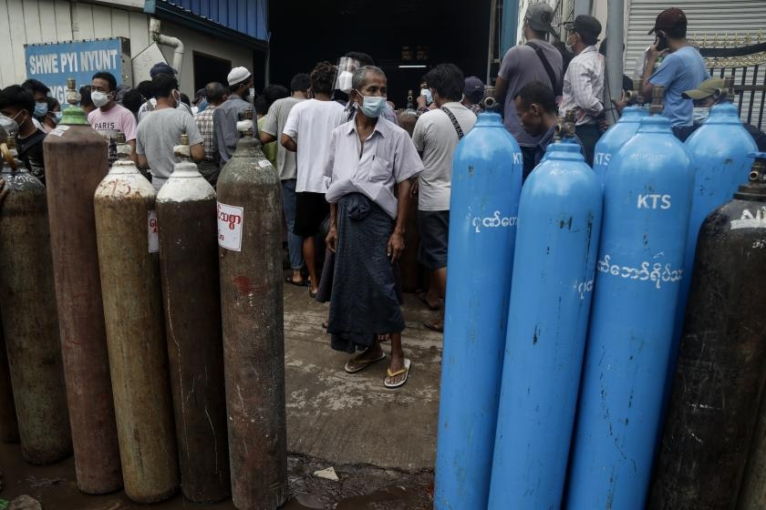 Industrial oxygen containers stand in front of a crowd of people on an Asian street.