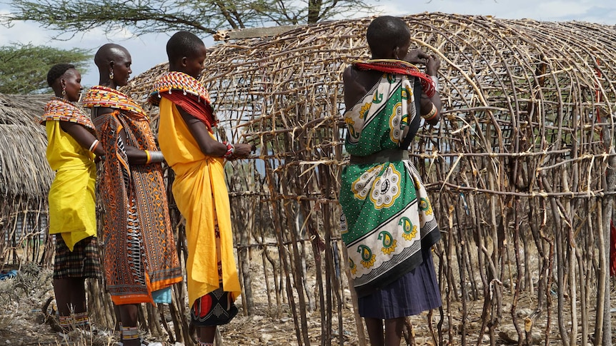 Some of Unity village women building a hut within the village
