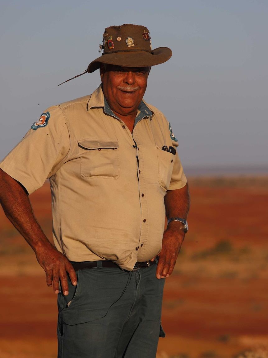 A man in an Akubra-style hat and a ranger uniform stands with hands on his hat with red dirt in the background.