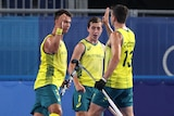 Three Australian hockey players high five each other on the field, they look excited and sweaty