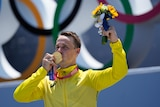 A man in a yellow jacket kisses the gold medal around his neck. He also holds a small bouquet of flowers in the air.