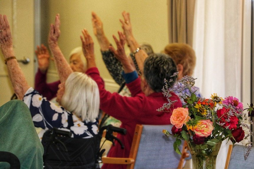 Aged care residents with arms in the air