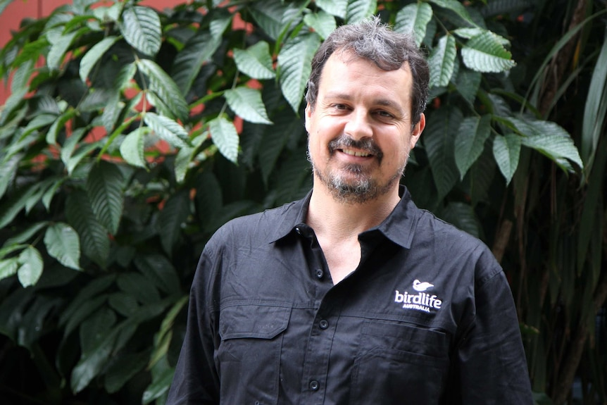A man with a short moustache and beard wearing a black shirt with a Birdlife Australia logo on the breast.