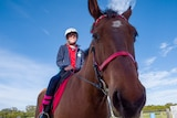 Close up of brown horse, with rider Aleisha on the saddle, she is smiling and wears a red shirt and blue jacket.