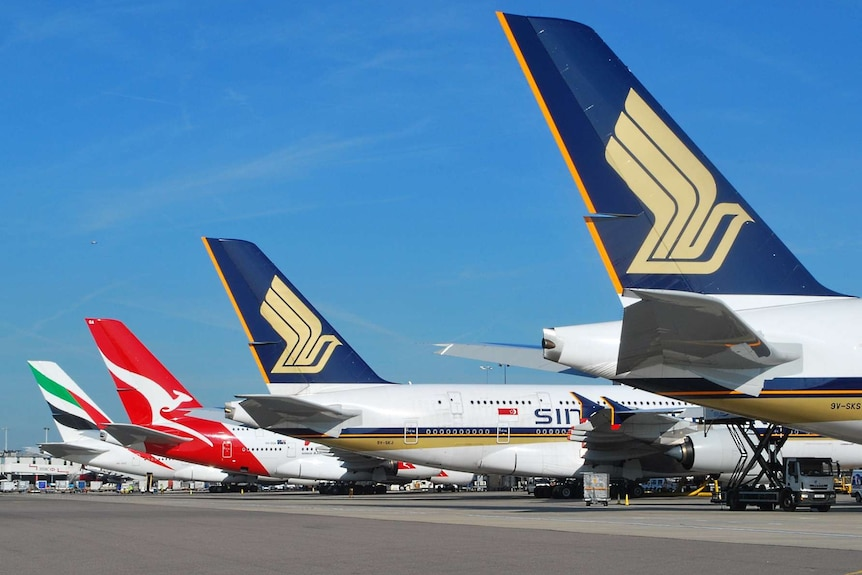 Against a blue sky, the tails of four Airbus A380 aircraft are shown descending diagonally down a runway.
