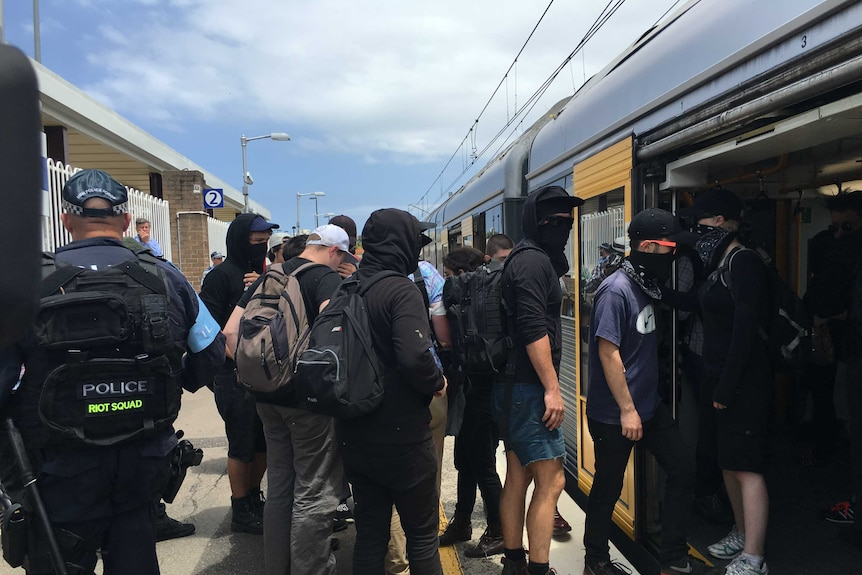A group of hooded and masked young men board a train with police behind them.