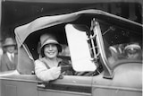 Black and white picture of Beryl Mills smiling, inside a car she won.