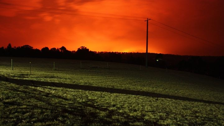 A glowing orange sky hangs over a green paddock, lit by bright spotlights.