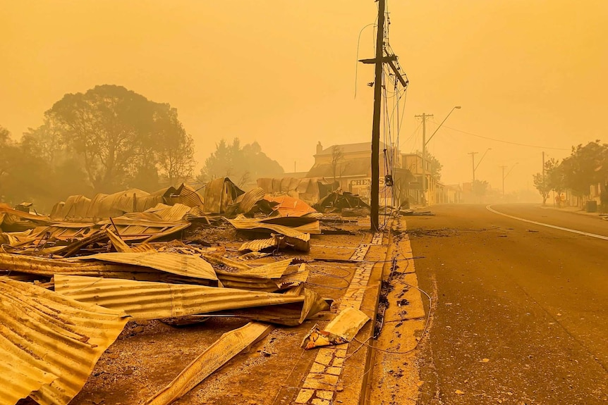 Main street of Cobargo with buildings in ruin and smoky sky.