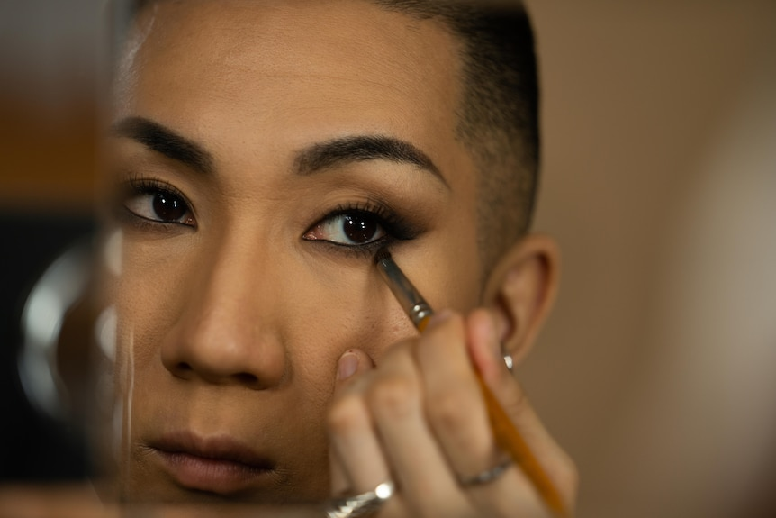 A Japanese man with a buzz cut brushes dark shadow under his eye