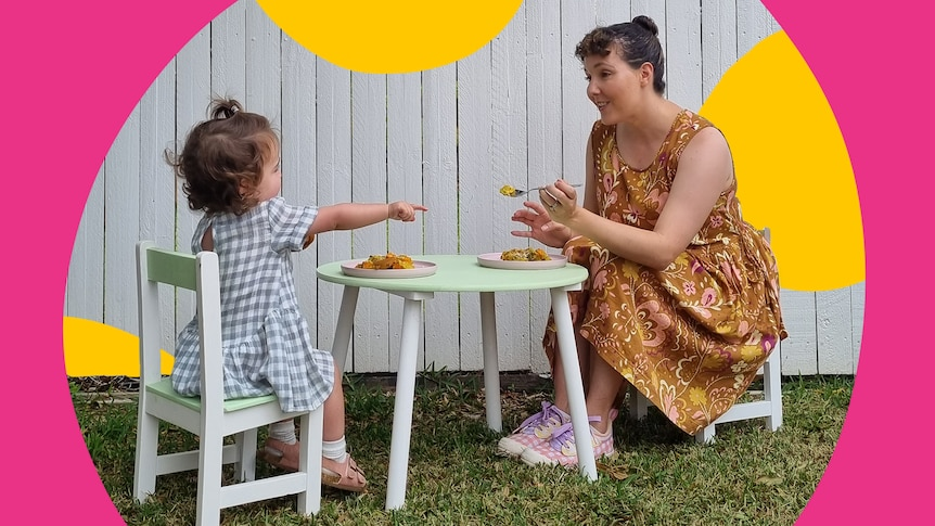 A toddler sits at an outdoor kids table while her mum tries to feed her dinner, the challenges of getting toddlers to eat.