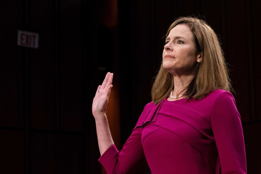 A woman raises her right palm and looks ahead as she stands to swear an oath of office.