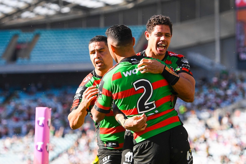 Three South Sydney NRL players embrace as they celebrate a try scored against the Newcastle Knights.