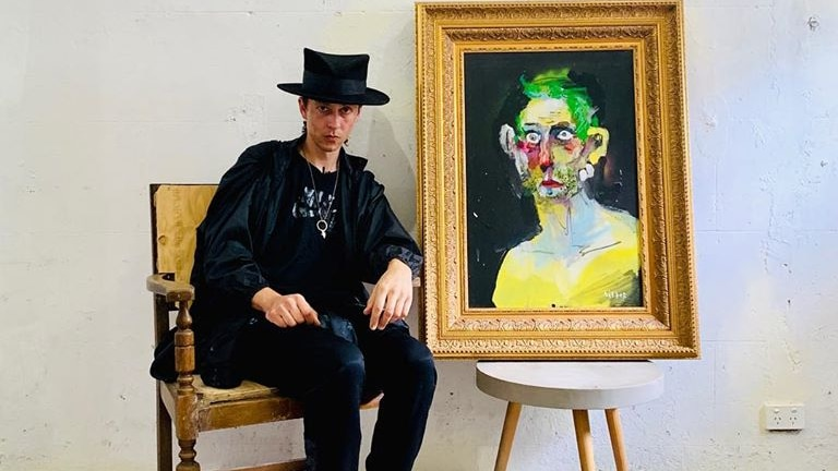 Anthony Lister sits wearing hat next to a painting of a man