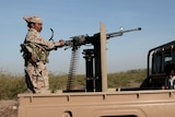 A soldier stands on the back of a ute.