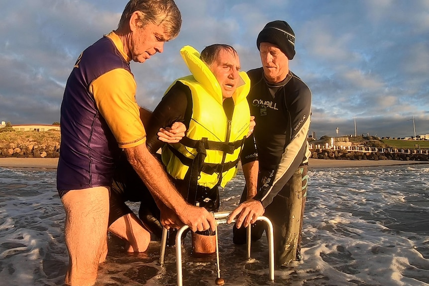 Man in ocean with life jacket with walking frame and two friends helping