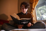 A studious-looking boy sits cross-legged and reads a book by a window.