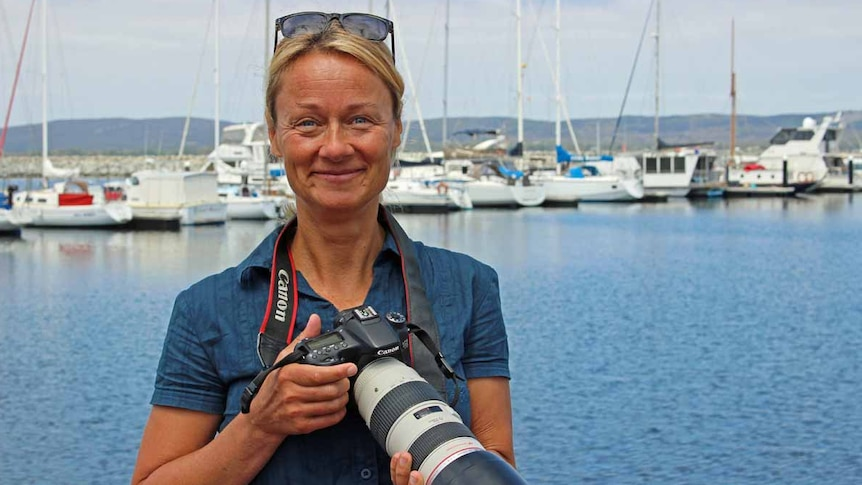 A woman with blonde hair stands in front of a marina holding a large camera.