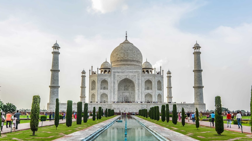 A front on view of the Taj Mahal with tourists walking towards it