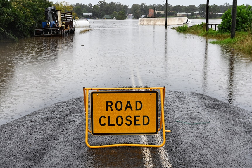 A road closed sign and flooded street
