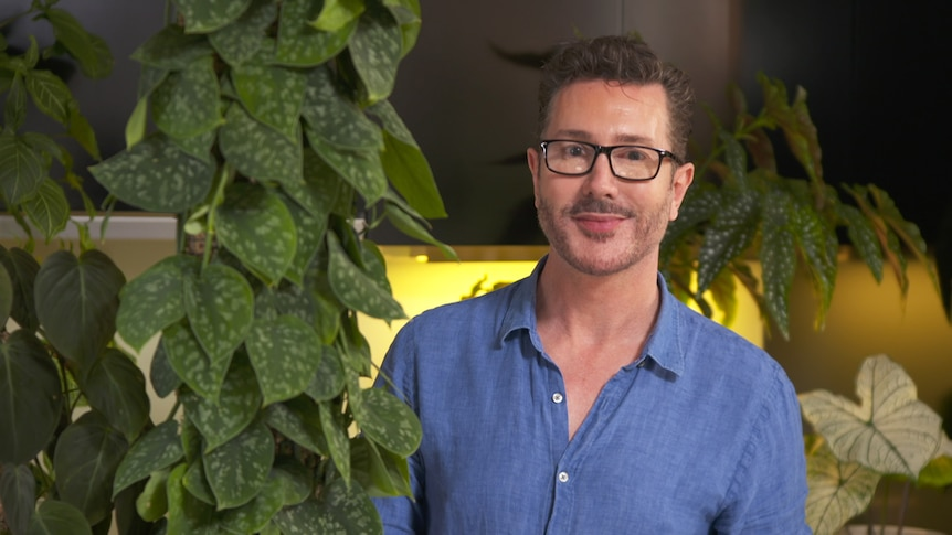 Craig Miller-Randle poses with indoor plants grown on totems, bulked up with propagation.
