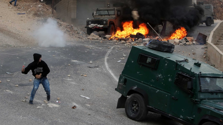 A Palestinian young man throws a bottle towards vehicles of Israeli security forces