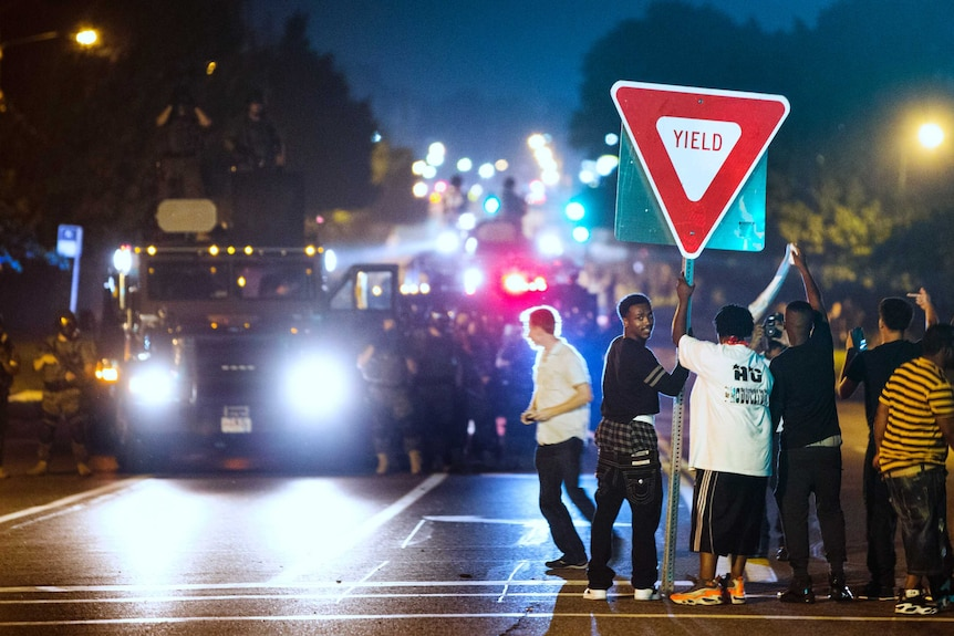 Members of a rowdy group of demonstrators stand with a road sign in Ferguson