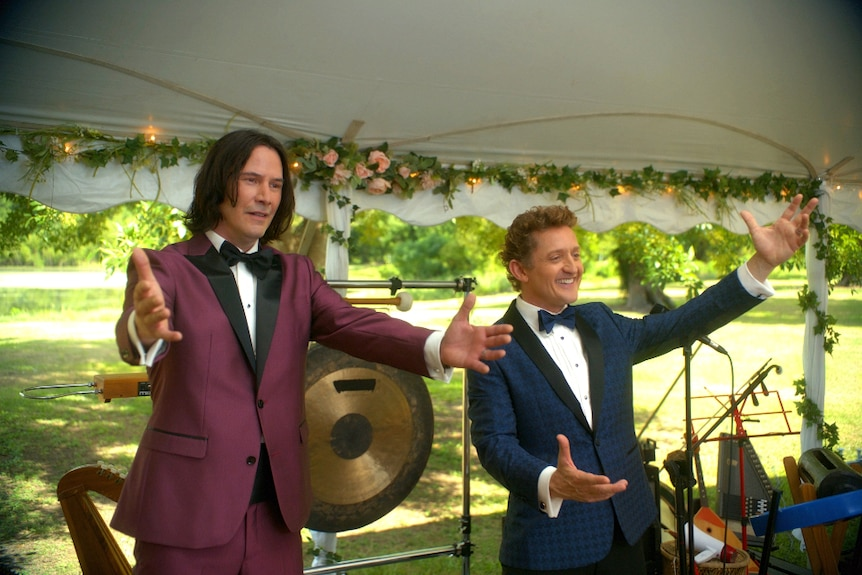 In outdoor tent on sunny day a dark haired man in maroon tux and shorter man in navy houndstooth suit stand with open arms.