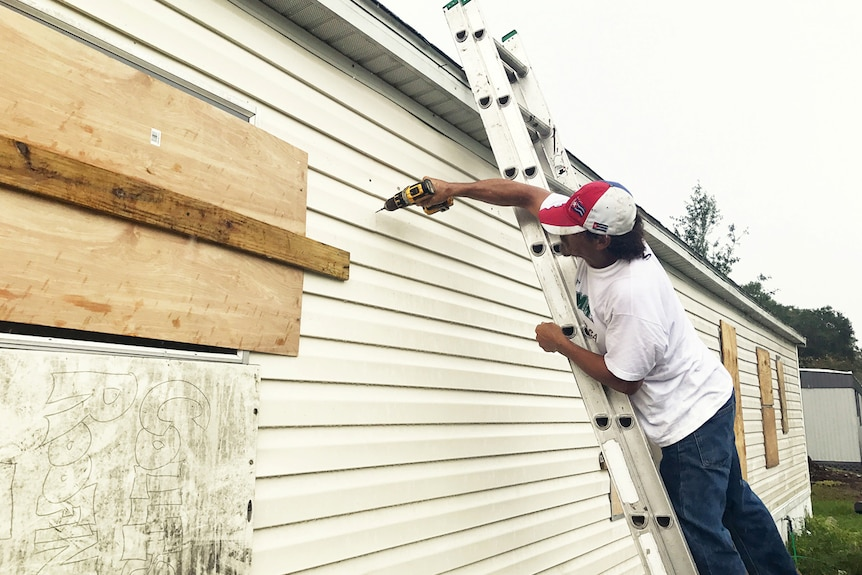 A man reinforces drills boards over windows as he reinforces his mobile home.